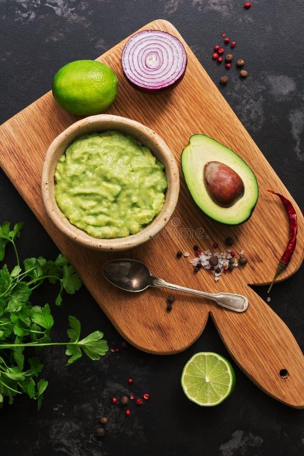 Traditionele Latijns-Amerikaanse Mexicaanse Guacamole-Saus in een kleikom Ingrediënten voor guacamole-avocado, rode ui, koriander stock fotografie
