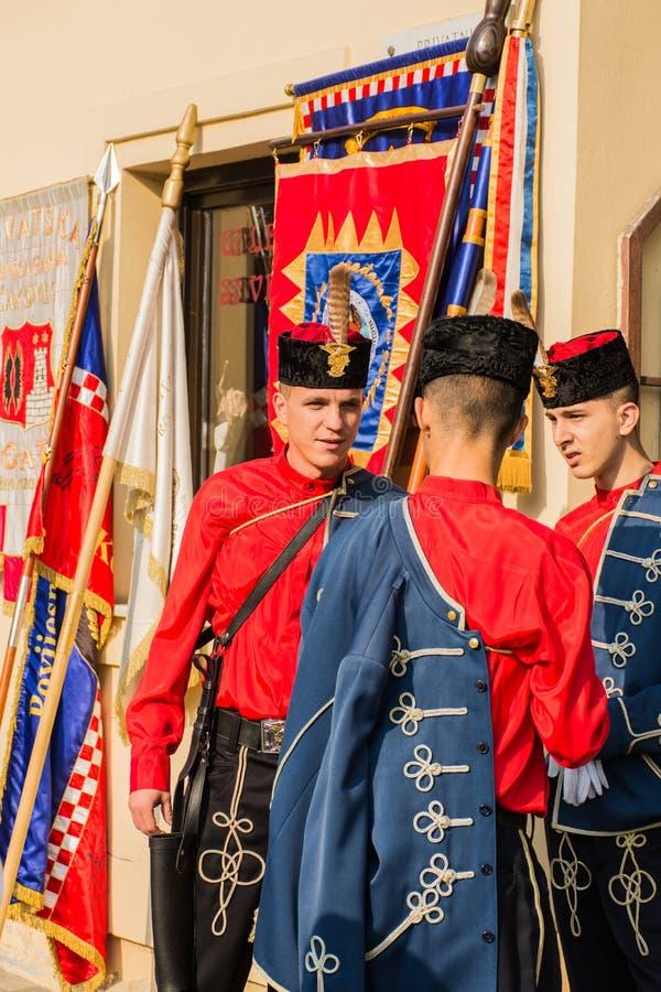 Traditionele militairen die op parade wachten die traditionele uniformen en hoeden draagt stock fotografie
