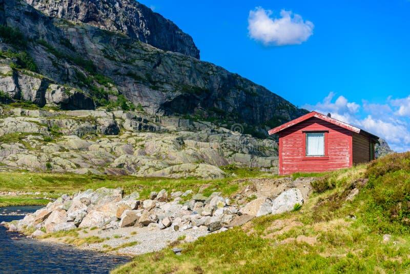 Traditionele mooie Noorse rode cabine op een meerkust royalty-vrije stock afbeeldingen