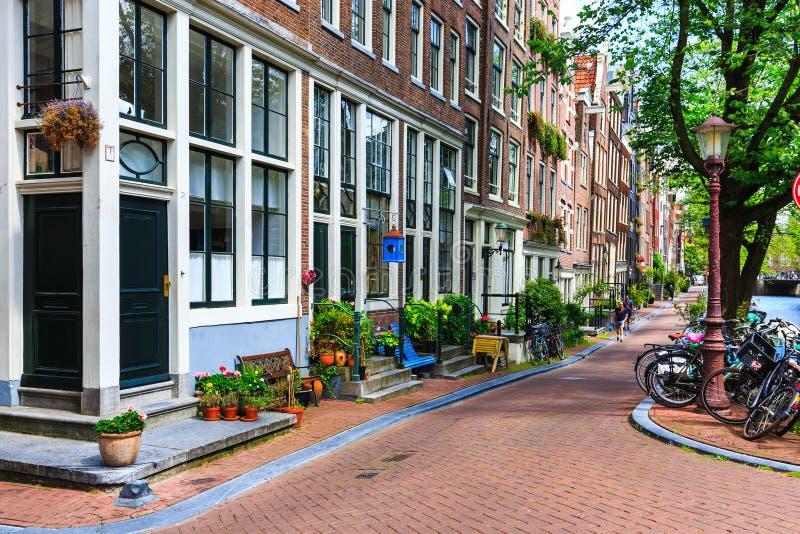 Traditionele Nederlandse die huizen, fietsen op stadsstraat bij de zomer worden geparkeerd De typische architectuur van Holland b stock fotografie