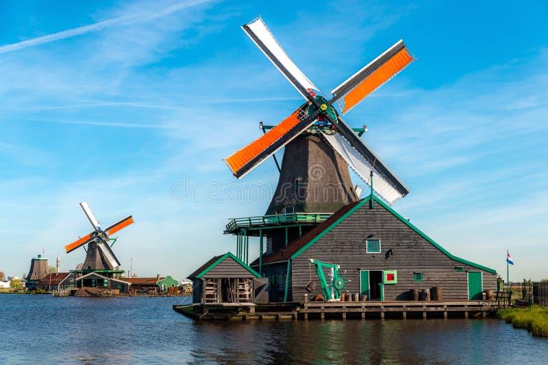 Traditionele Nederlandse die windmolens door de rivier Zaan, in Zaanse Schans, Nederland worden gevestigd royalty-vrije stock foto