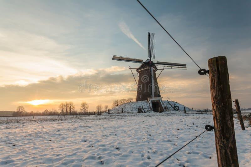 Traditionele Nederlandse windmolen in de winter tijdens zonsondergang stock foto