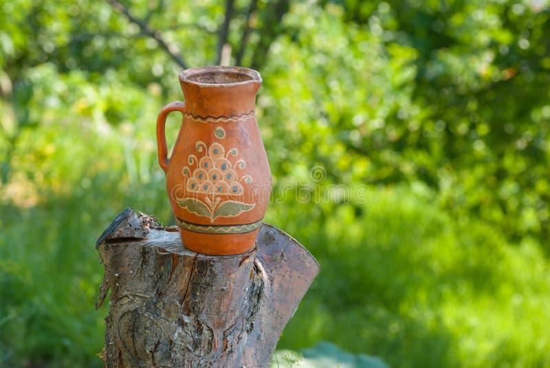 Traditionele Oekraïense kleipot die zich op een besnoeiingsboom bevinden in de zomertuin stock fotografie