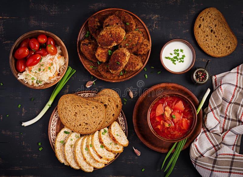 Traditionele Oekraïense Russische borscht of rode soep met sappige heerlijke vleeskoteletten stock afbeeldingen
