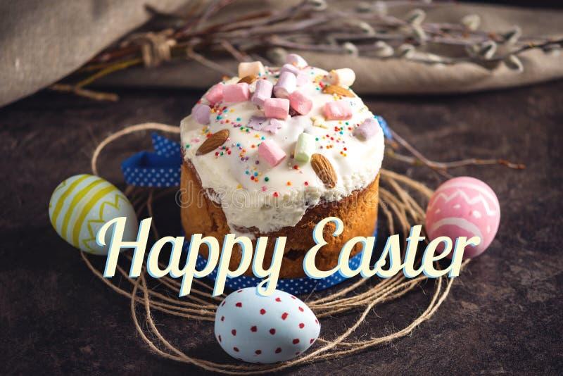 Traditionele Pasen-cake en kleurrijke eieren en tekst in rustieke stijl op een donkere achtergrond De kaart van de vakantie stock afbeeldingen