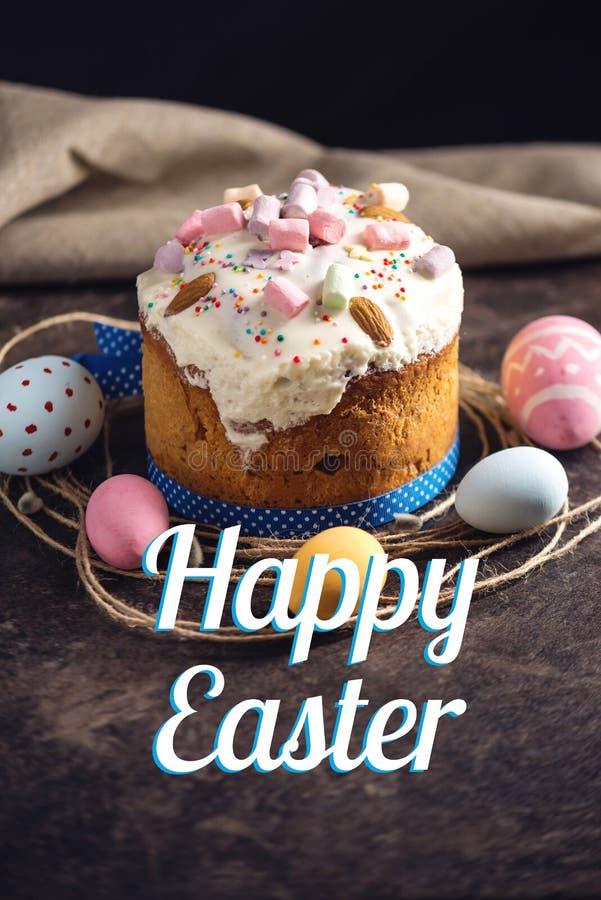 Traditionele Pasen-cake en kleurrijke eieren en tekst in rustieke stijl op een donkere achtergrond De kaart van de vakantie royalty-vrije stock foto
