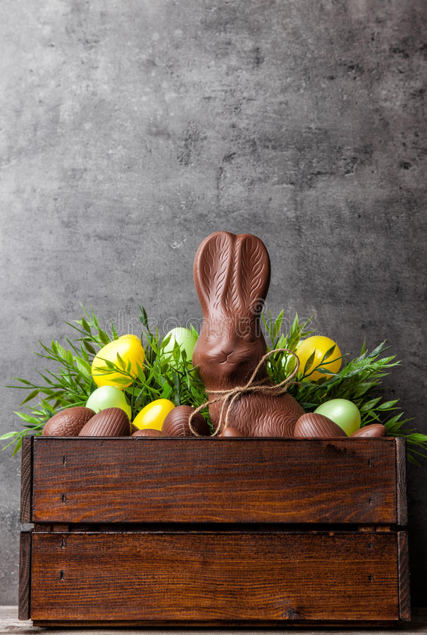 Traditionele Pasen-chocoladekonijntje en eieren binnen een houten krat stock foto