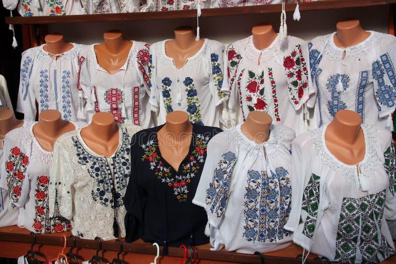 Traditionele Roemeense volksdieblouses voor verkoop bij één traditionele markt worden blootgesteld stock fotografie