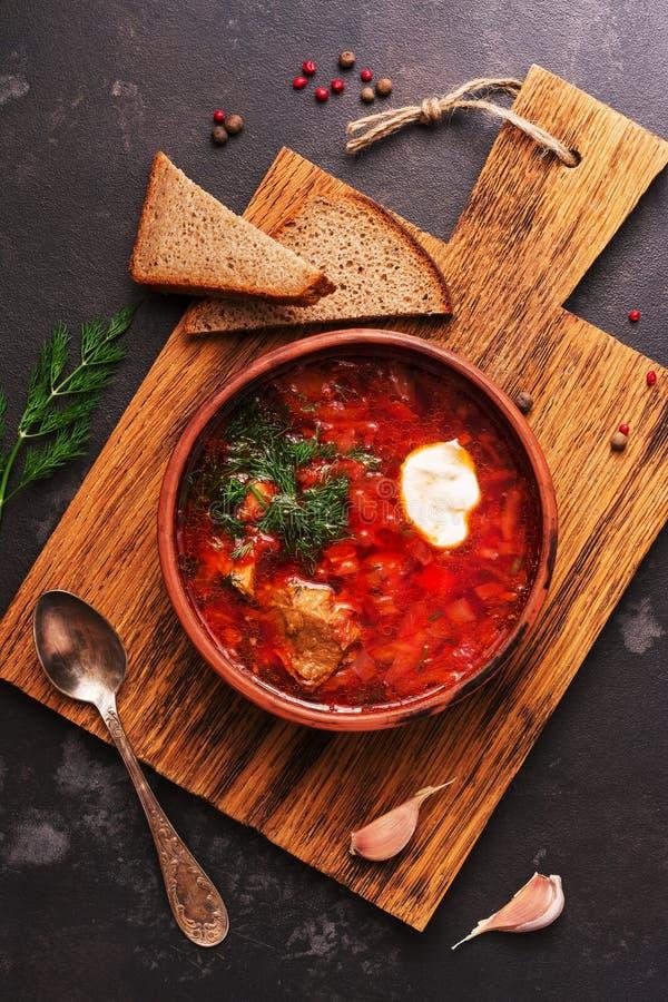 Traditionele Russische Oekraïense borscht rode soep met roggebrood op een donkere achtergrond Borsjt met vlees, zure room en dill royalty-vrije stock foto's