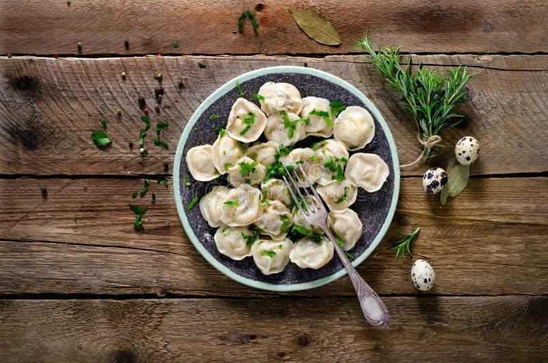Traditionele Russische pelmeni, ravioli, bollen met vlees op houten lijst met bloem, peterselie, kwartelseieren, peper royalty-vrije stock afbeeldingen