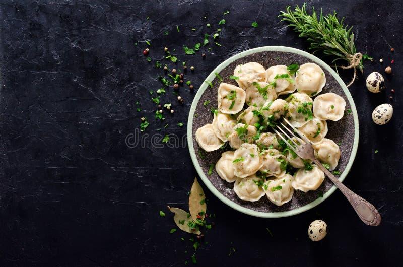 Traditionele Russische pelmeni, ravioli, bollen met vlees op zwarte concrete achtergrond Peterselie, kwartelseieren, peper stock afbeeldingen