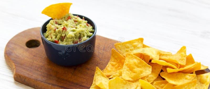 Traditionele saus guacamole met nachos op rustieke houten raad op witte houten oppervlakte Zachte nadruk Close-up stock afbeelding