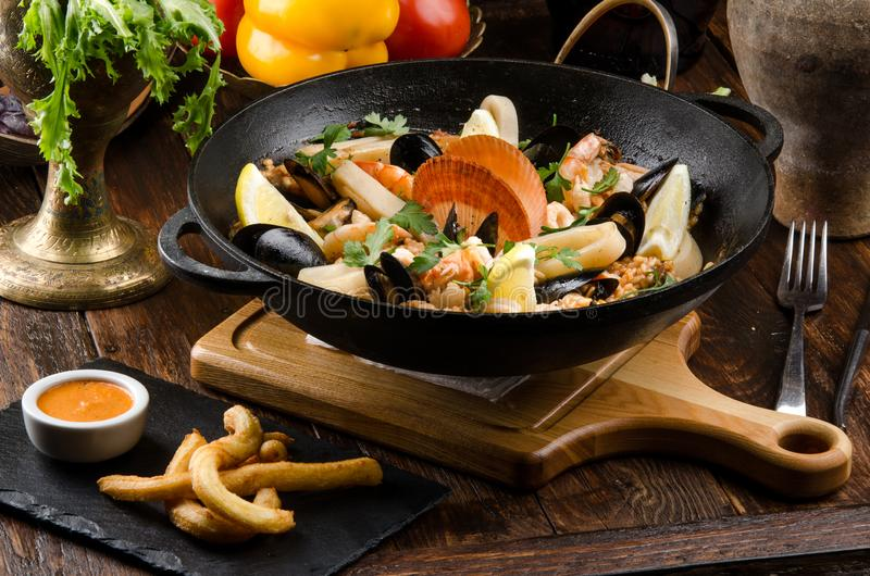 Traditionele Spaanse schotelpaella met zeevruchten: garnalen, pijlinktvissen, mosselen, wijn, citroen en rijst in een zwarte kete stock afbeeldingen