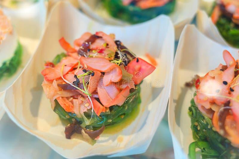 """Traditionele Spaanse tapas met verse zeevruchten dienden in kleine kop†""""heerlijke pijlinktvis met gemarineerde zeewiersalade royalty-vrije stock foto"""