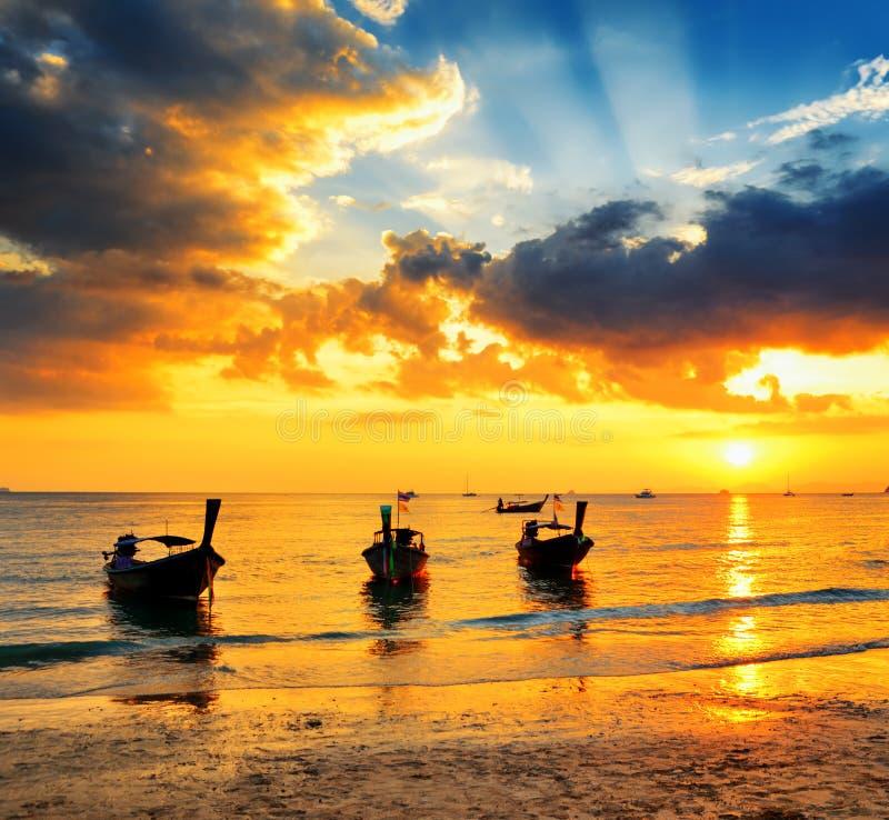 Traditionele Thaise boten bij zonsondergangstrand stock foto