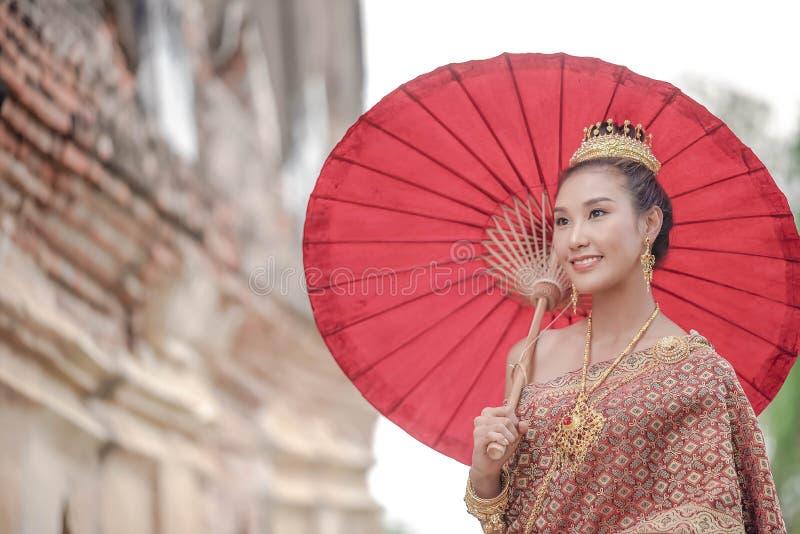 Traditionele Thaise kleding Mooie vrouwen die een traditionele Thaise doek dragen als huwelijkskleding die een rode paraplu openl royalty-vrije stock fotografie