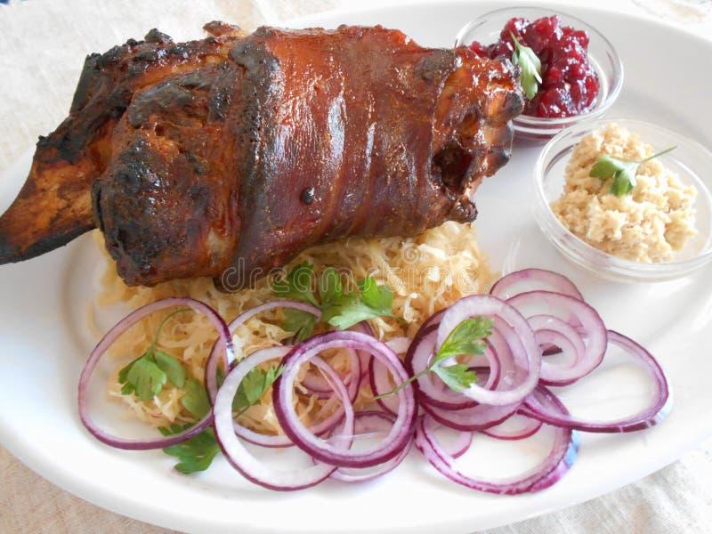 Traditionele Tsjechische schotel van geroosterd varkensvleesbeen met verse rode uien, horseredish, zuurkool, Amerikaanse veenbess stock foto's