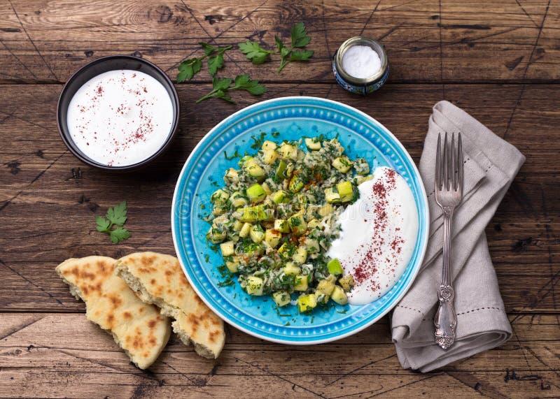 Traditionele Turkse gebraden eieren met courgette en kruiden met de saus van het yoghurtknoflook en verse tortilla's op een houte stock fotografie