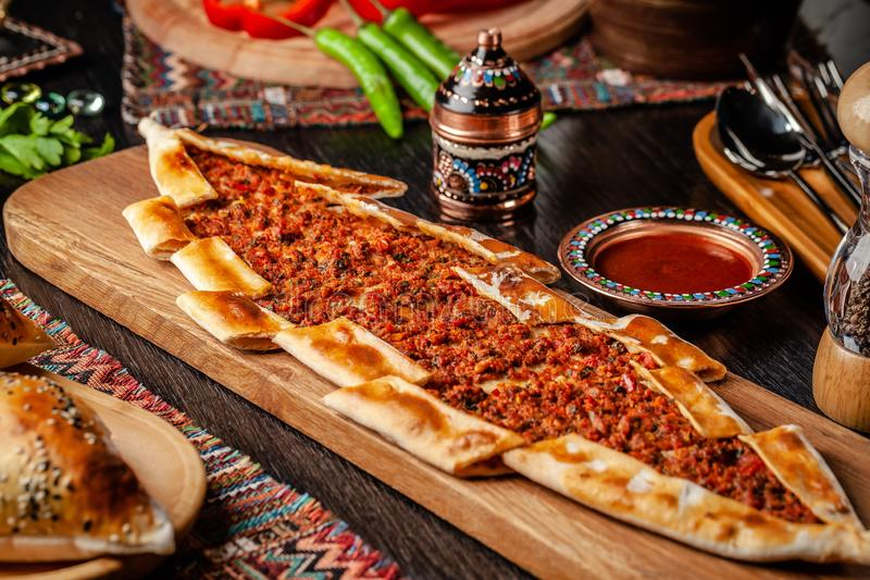 Traditionele Turkse pizza cuisine Turks pizzapitabroodje met vlees Turk Pidesi of Sucuk Pide Mooie dienende schotels in het resta stock foto's