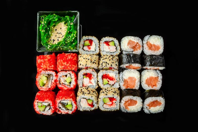 Traditionele verse Japanse sushibroodjes op een zwarte achtergrond stock foto's