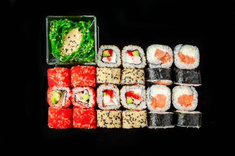 Traditionele verse Japanse sushibroodjes op een zwarte achtergrond stock foto