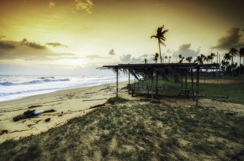 Traditionele visser op het strand groen gras en strandzand dramatische en zachte wolken met gele kleur tijdens zonsopgangzonsonde royalty-vrije stock afbeelding