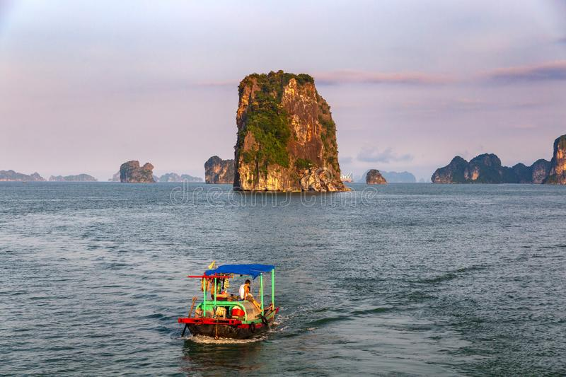 Traditionele vissersboot in Halong-Baai in een purpere zonsondergang, Unesco-wereldnatuurlijk erfgoed, Vietnam stock fotografie