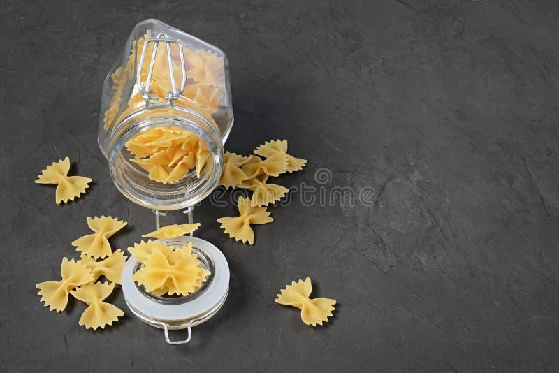 Traditionele vorm van droge ongekookte gehele tarwe Italiaanse deegwaren in glaskruik stock foto's