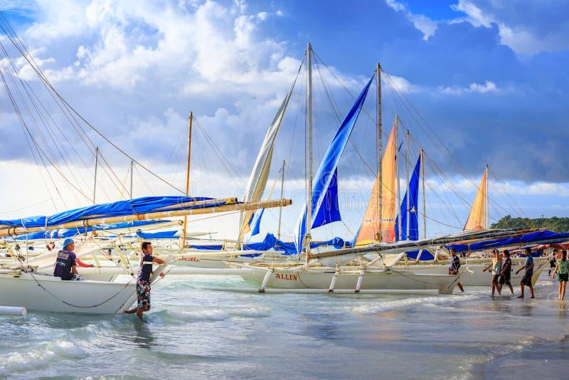 Traditionele Zeilboten op Overvol Boracay-strand stock afbeeldingen