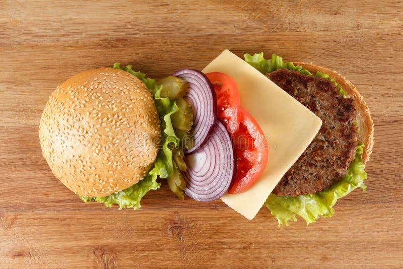Traditionell amerikansk ostburgare Kött, bullen och grönsaker stänger sig upp royaltyfri foto