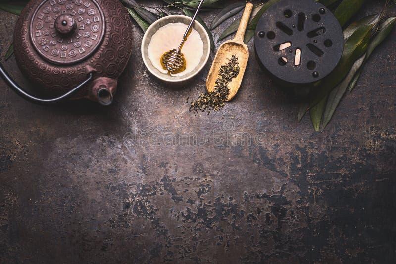 Traditionell asiatisk bakgrund för grönt te med den svarta den järntekannan, stearinljuset och honung på mörk lantlig bakgrund me arkivbilder