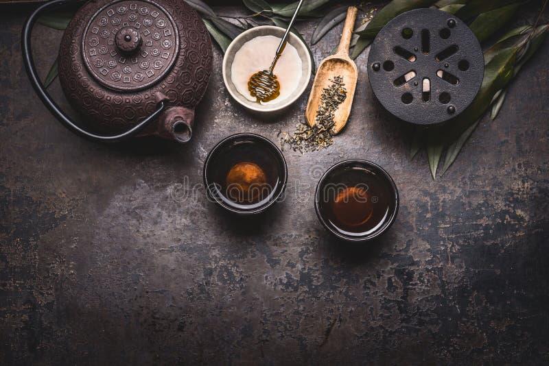Traditionell asiatisk inställning för grönt te med tekannan, koppar, stearinljuset och honung på mörk lantlig bakgrund med kopier royaltyfri bild