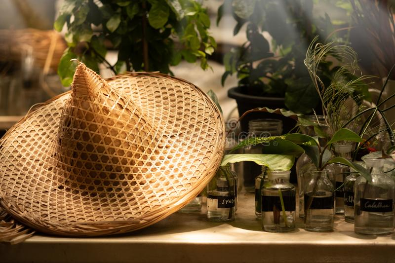 Traditionell asiatisk konisk bambuhatt på den gamla tabellen med blomman in arkivfoton