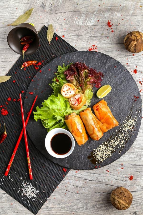 Traditionell asiatisk mat, stekte rullar med sallad och grönsaker på den svarta plattan royaltyfri foto