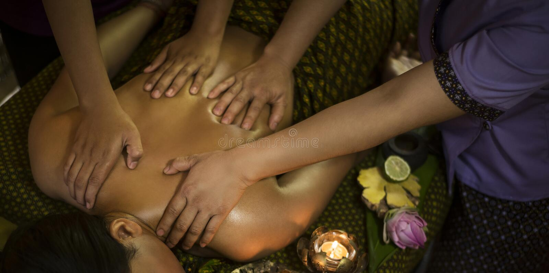 Traditionell asiatisk thai massage för fyra hand i tropisk brunnsort arkivfoto