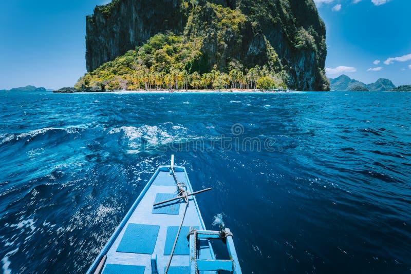 Traditionell bancafartyginställning en liten Ipil strand framme av den runda Pinagbuyatan ön med enorma kalkstenklippor royaltyfria foton