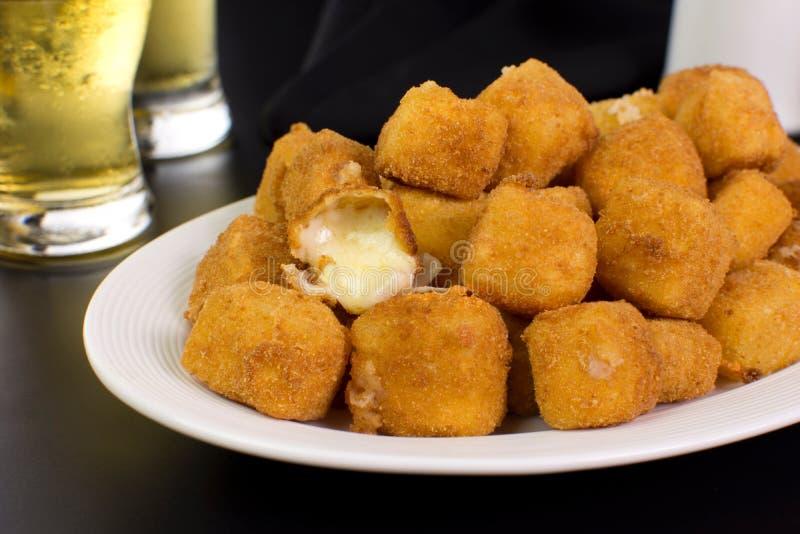 Traditionell brasiliansk pub-ost med livsmedelsprovolon i breda smulor som kallas provolone a milanesa nära en öppen i ett svart  arkivfoton