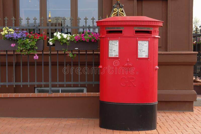 Traditionell brittisk röd stolpeask på gatan royaltyfri foto