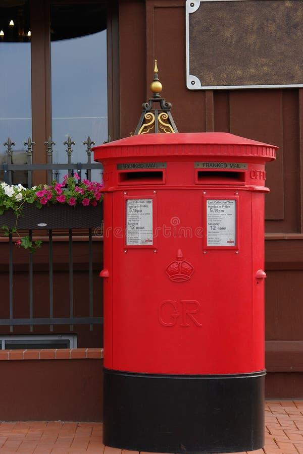 Traditionell brittisk röd stolpeask på gatan arkivbild