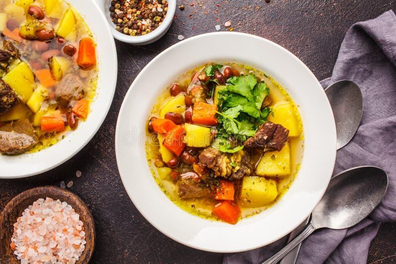 Traditionell eintopfsoppa med kött, bönor och grönsaker i en vit platta arkivfoto