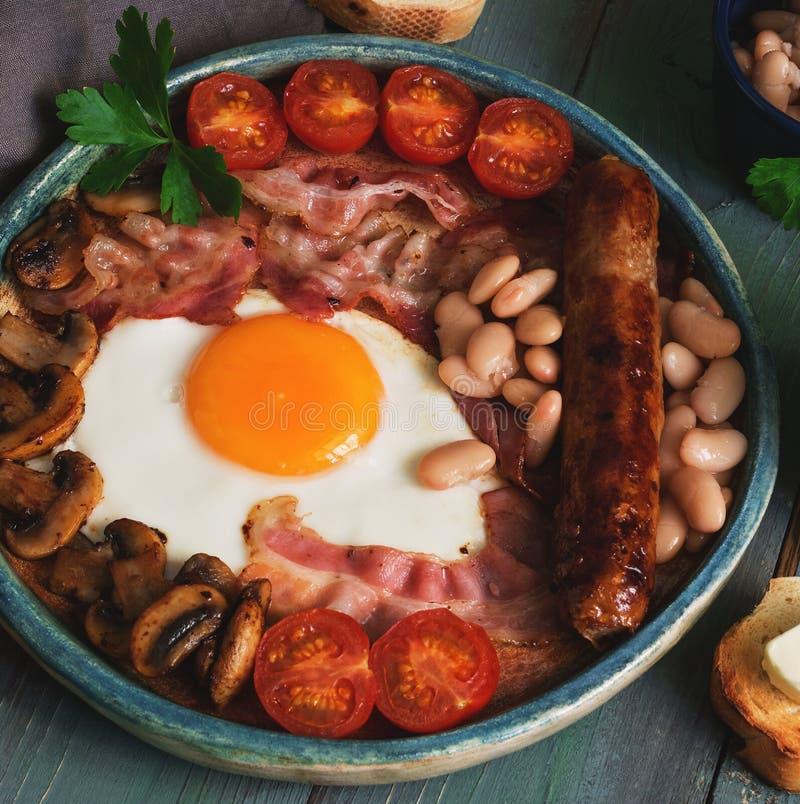 Traditionell engelsk frukost, förvanskade ägg, bacon, champinjoner, korv, bönor och körsbärsröda tomater på en lantlig plankatabe fotografering för bildbyråer