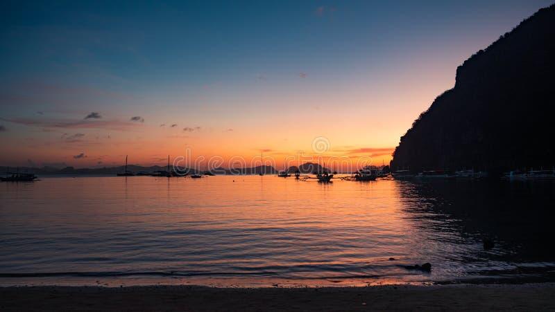 Traditionell filébangka vid solnedgången Vackra solnedgången med silhuetter av filtbåtar, El Nido, Palawan, royaltyfria bilder