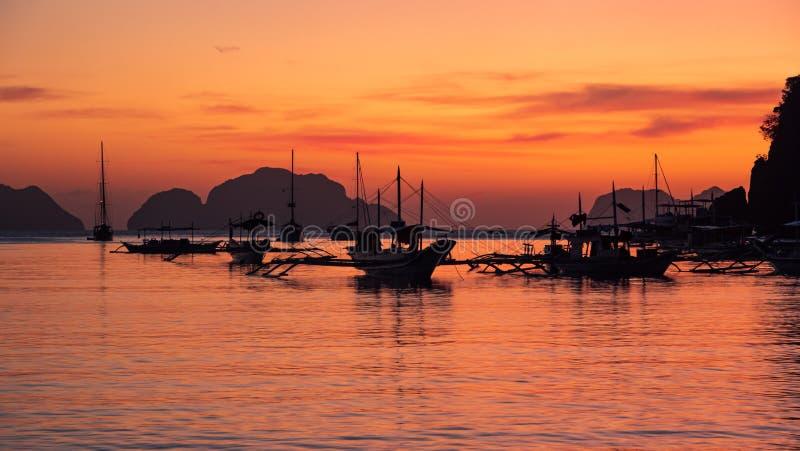 Traditionell filébangka vid solnedgången Vackra solnedgången med silhuetter av filtbåtar, El Nido, Palawan, royaltyfri fotografi