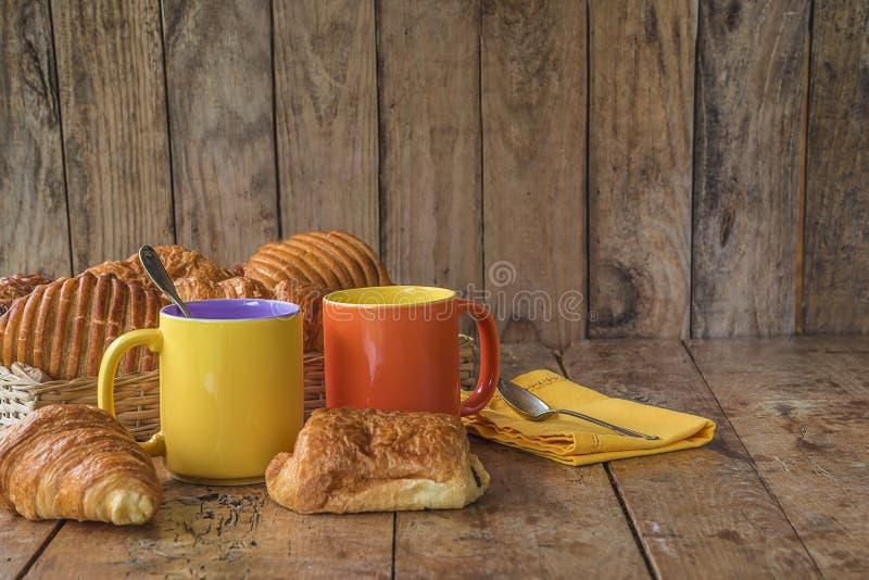 Traditionell fransk frukost med varma kaffe och giffel: den vide- korgen med giffel, chokladbröd, två rånar av kaffe på royaltyfri bild