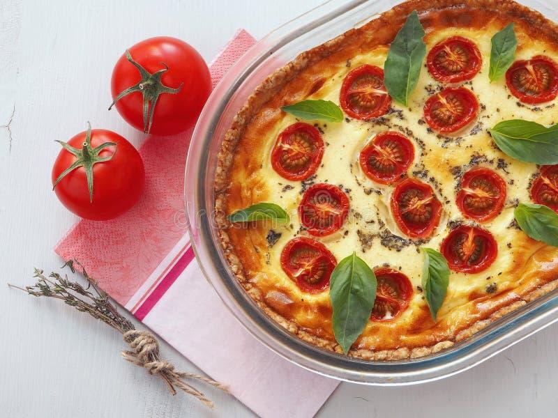 Traditionell fransk pajpaj Hemlagat syrligt med sidor för körsbärsröda tomater, purjolök- och basilika Vegetarisk gratäng arkivbild