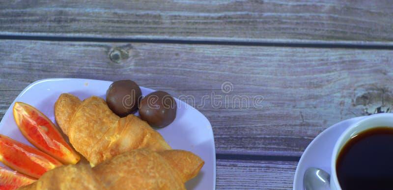 Traditionell frukost, en kopp av svart kaffe, giffel, orange skivor och choklader Landskap royaltyfria foton