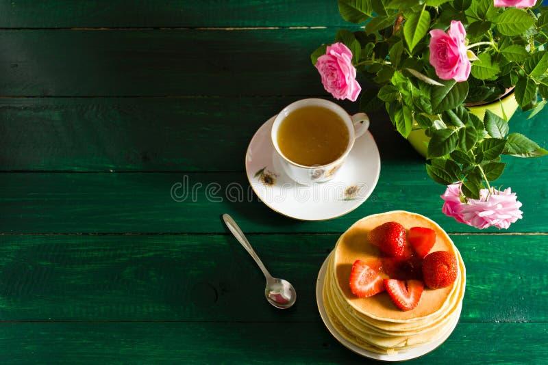 Traditionell frukost: pannkakor med sirap och jordgubben, gräsplan royaltyfria foton