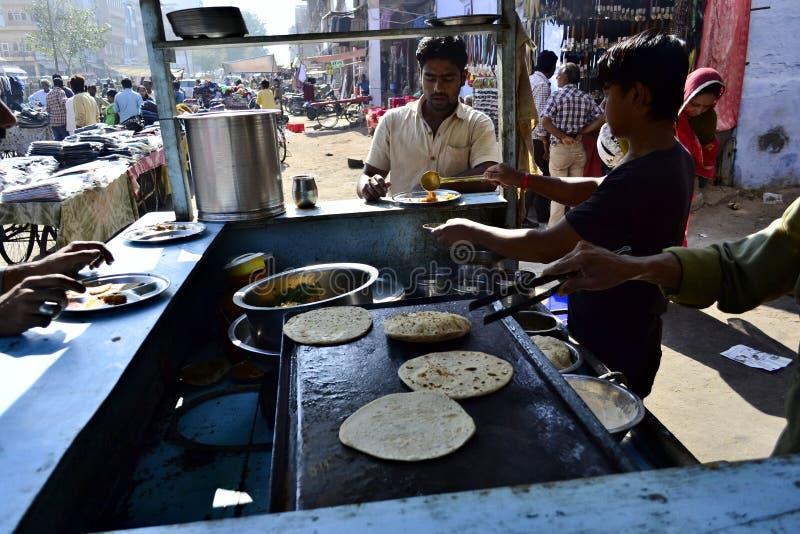 Traditionell gatamatförsäljare Mannen lagar mat och inverterar den indiska den tunnbrödrotien eller chapatien som tjänas som med  royaltyfri foto
