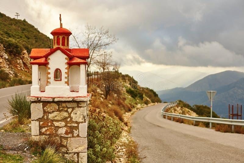 Traditionell grekisk liten kyrka nära vägen royaltyfria foton