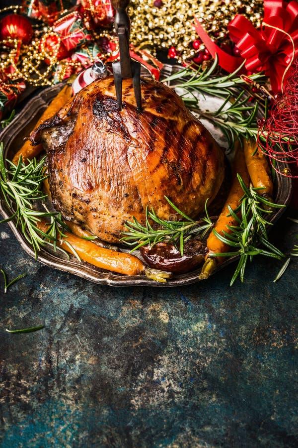 Traditionell grillad julskinka med stekgrönsaker på tappningplattan med festlig feriegarnering på mörk lantlig bakgrund royaltyfria foton